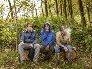 three men smoking in woods