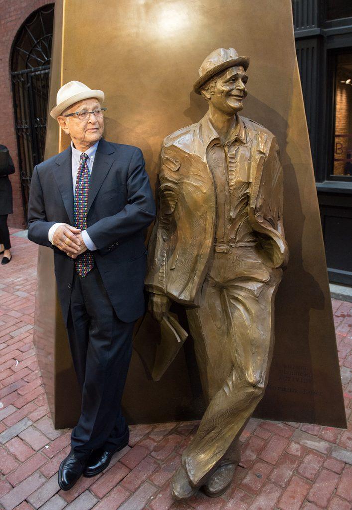 Norman Lear leans agains Norman Lear Sculpture