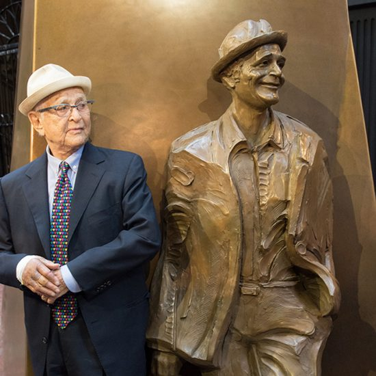 Norman Lear standing next to statue of himself