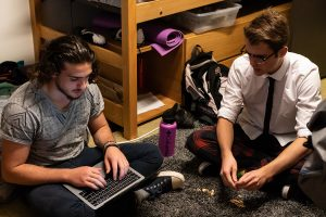 students on floor, one types on laptop