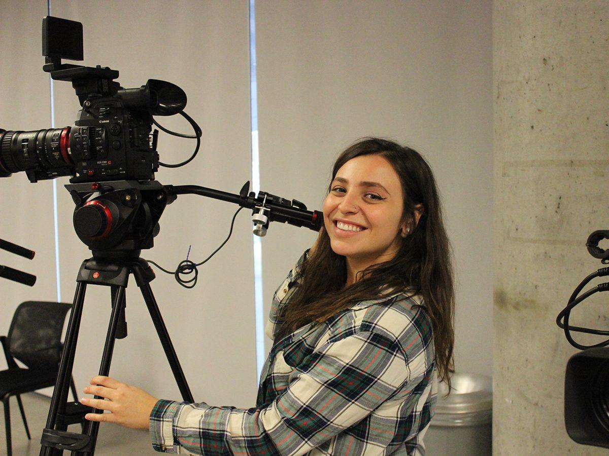 student behind camera