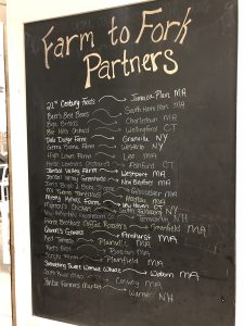A chalkboard displays farms that have produce being used at the dining hall.