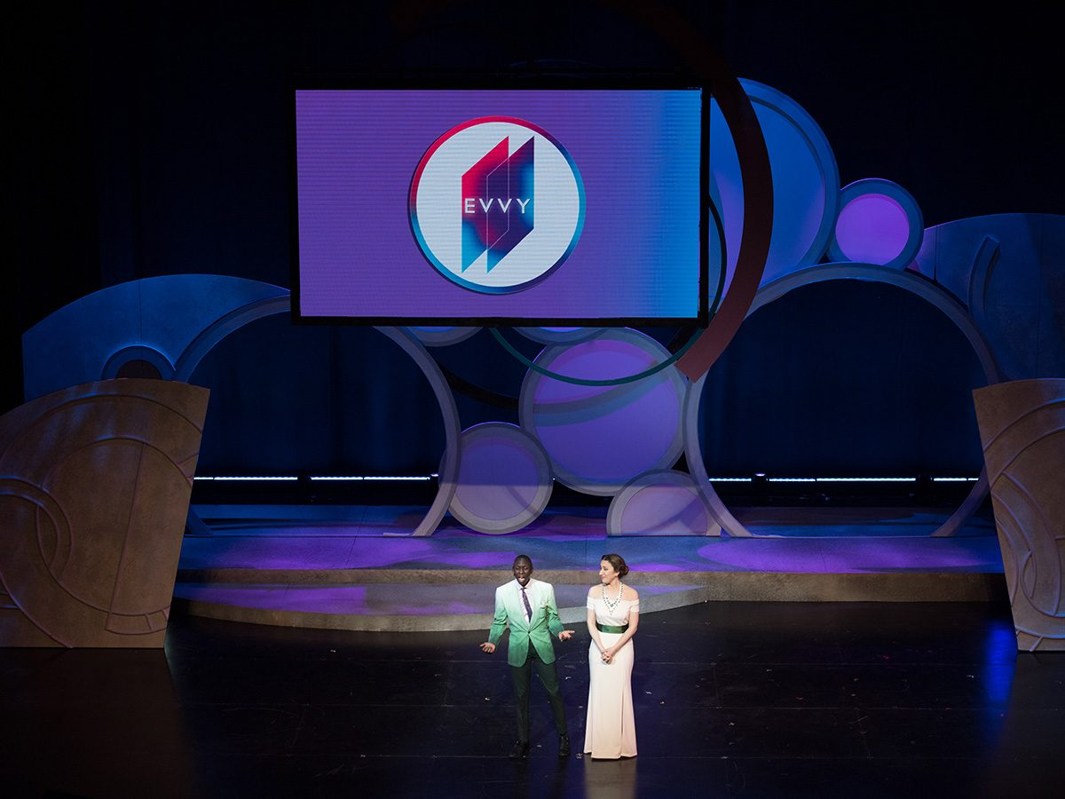 presenters on stage with elaborate set
