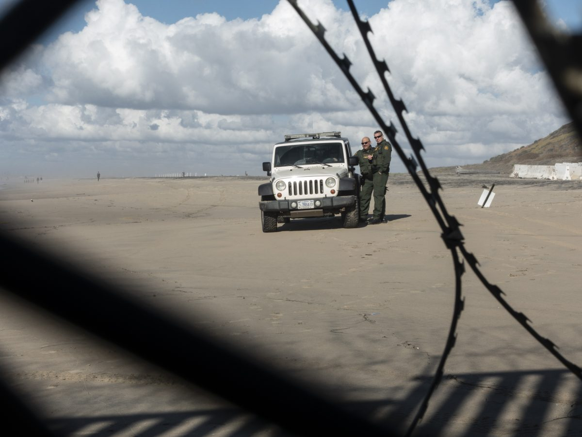 U.S. Border Patrol agents can be seen through a border wall and wire between the U.S. and Mexico.