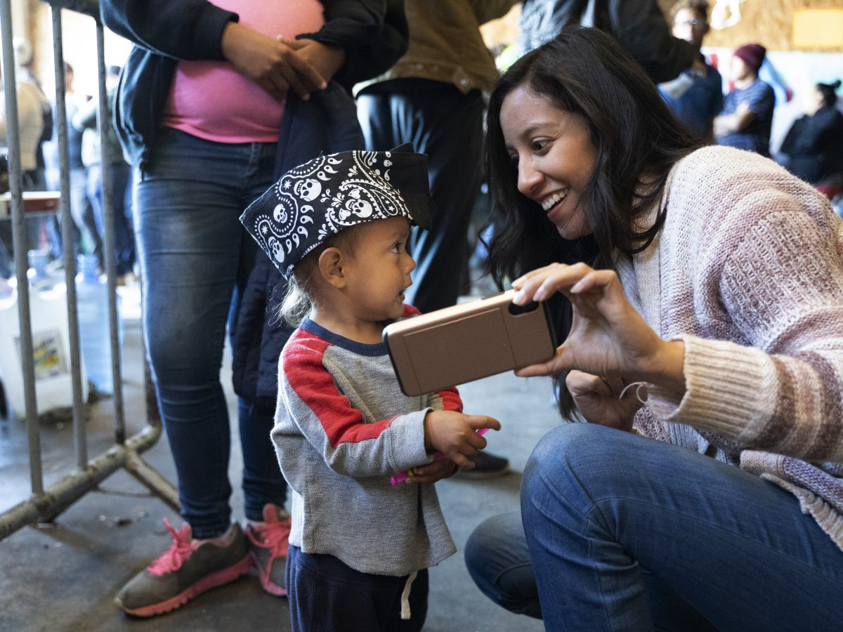 A humanitarian activist plays with a child at an immigrant shelter in Tijuana.