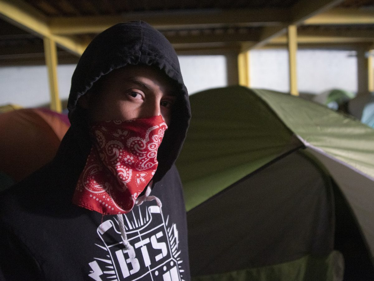 A detainee at the Mexican border wears a bandana to cloak his identity.