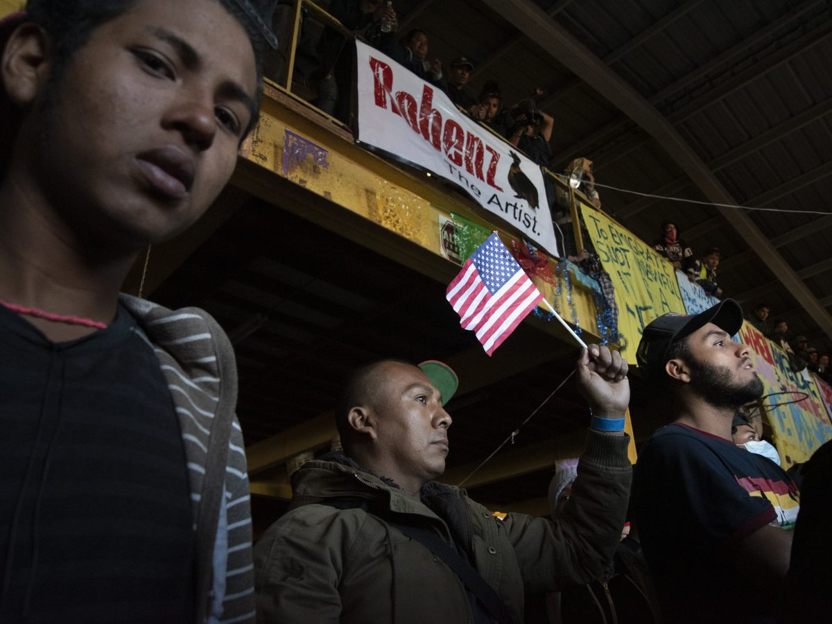 Individuals in a migrant shelter in the north district of Tijuana participate participate in a protest.