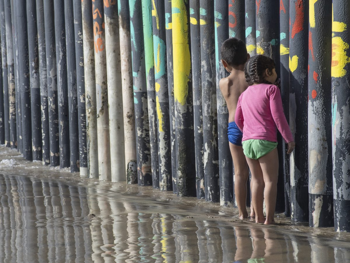 Two children look through a border wall on the beach in Tijuana.