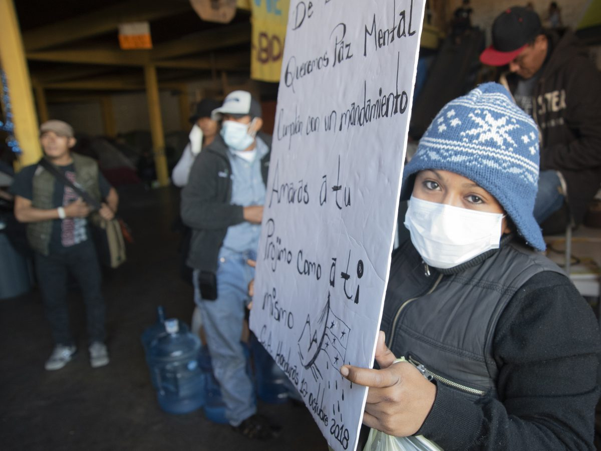 A Honduran immigrant displays a sign inside an immigrant shelter in Tijuana. She left Honduras to get away from a gang that killed the father of her child.