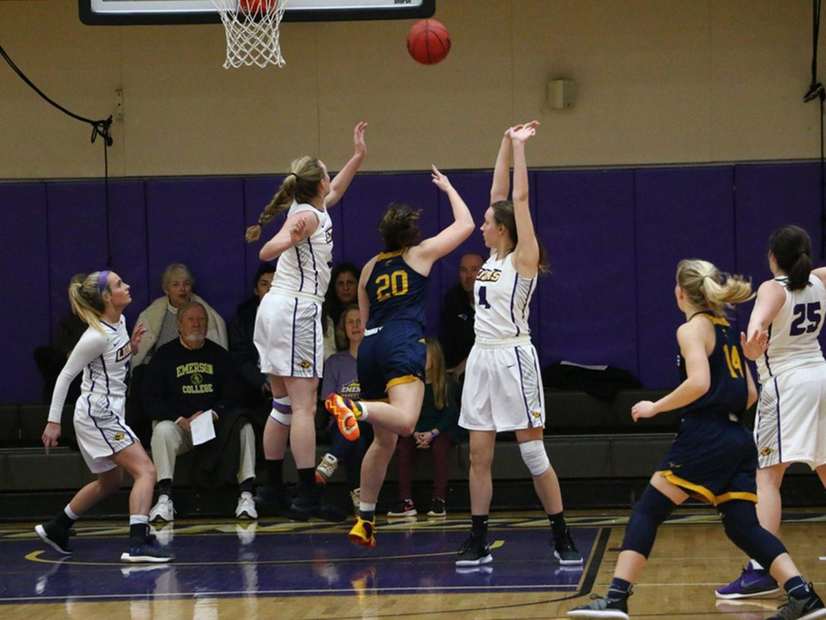 Emerson women basketball players go up for a shot