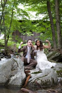 bride and groom flex muscles on rock