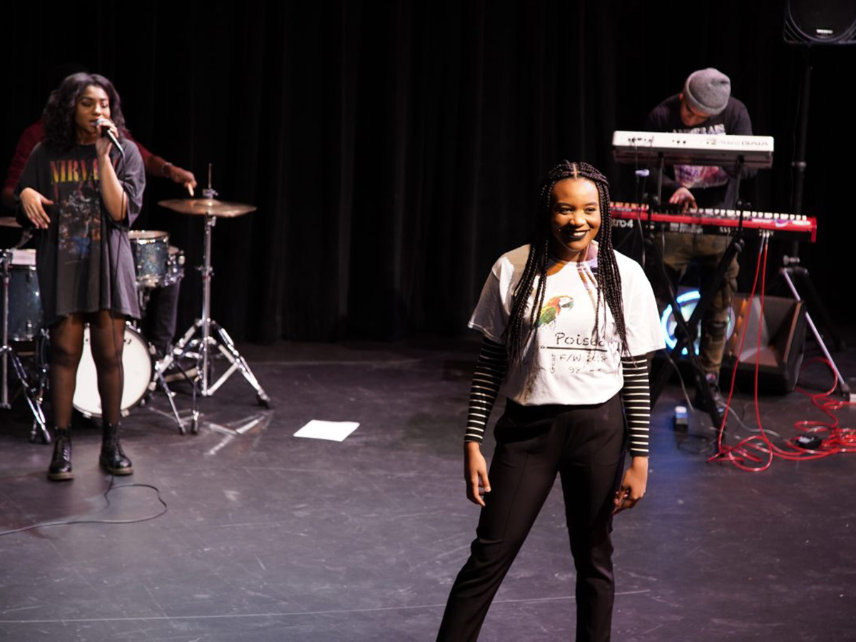 woman on stage poses with musicians