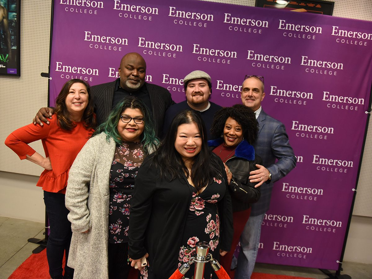 seven people in front of Emerson College step and repeat