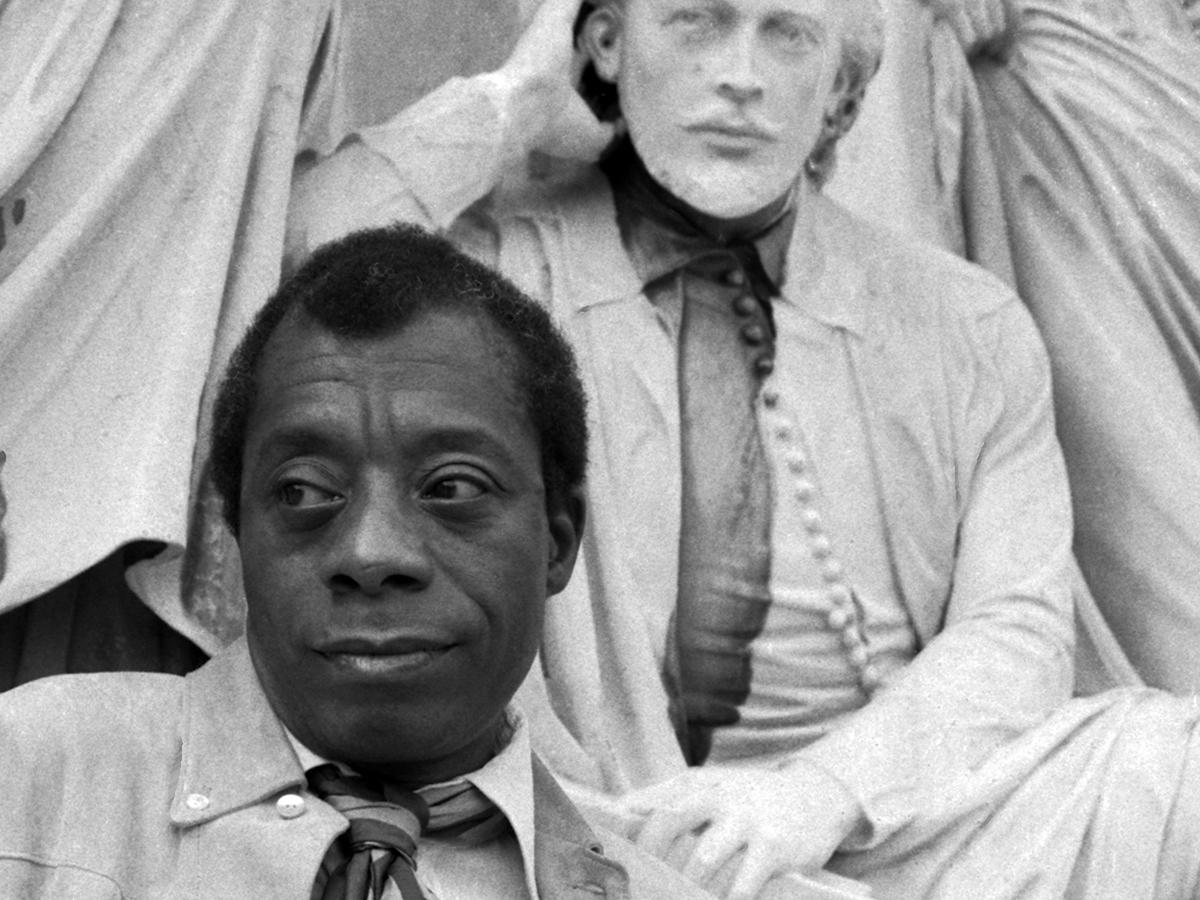 James Baldwin in front of statue