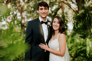 bride and groom surrounded by ferns