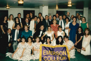 Large group of alums holding Emerson banner