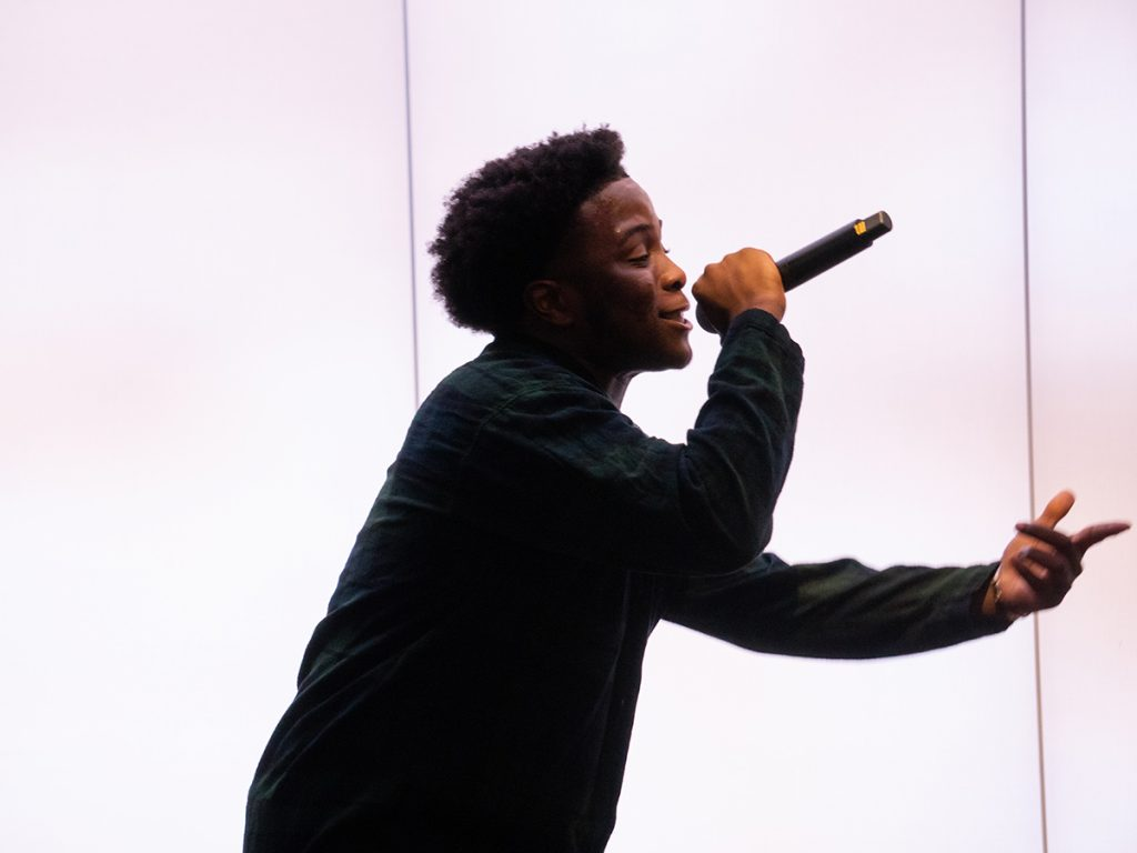 Young man with mic silhouetted against white