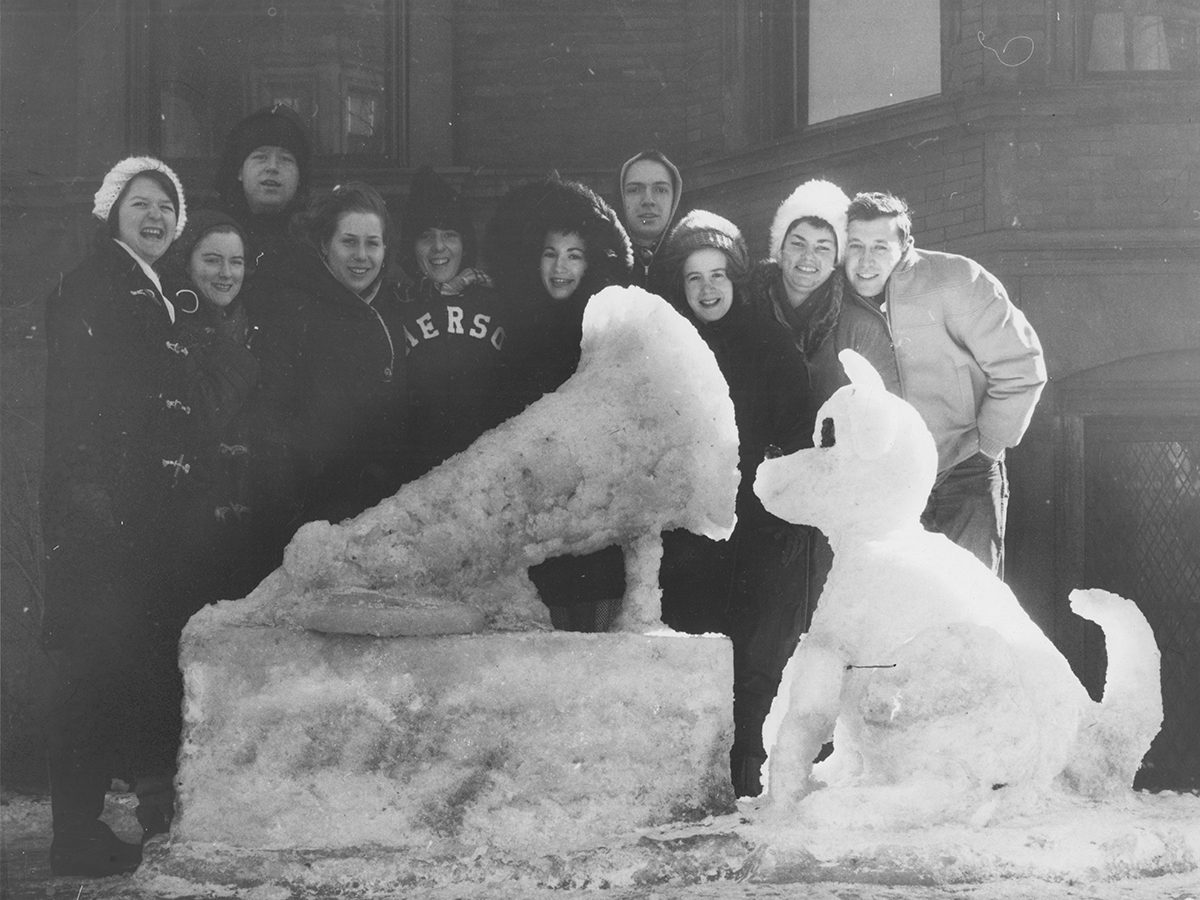 students stand behind snow sculpture of dog and gramophone, in black and white