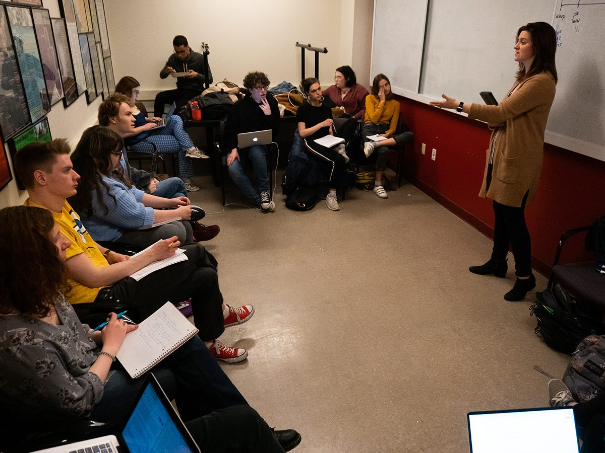 woman, standing, talks to seated class