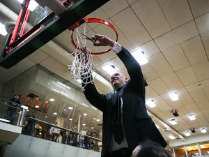 Mens basketball coach Bill Curley cuts down the net after the Emerson College Lions won the NEWMAC championship in 2019.