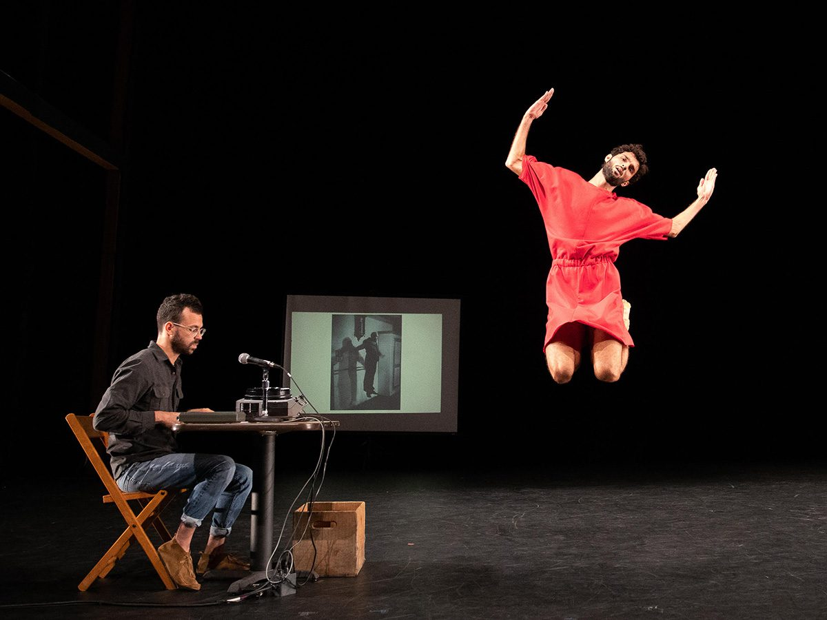 man seated at table behind mic; different man jumps in air