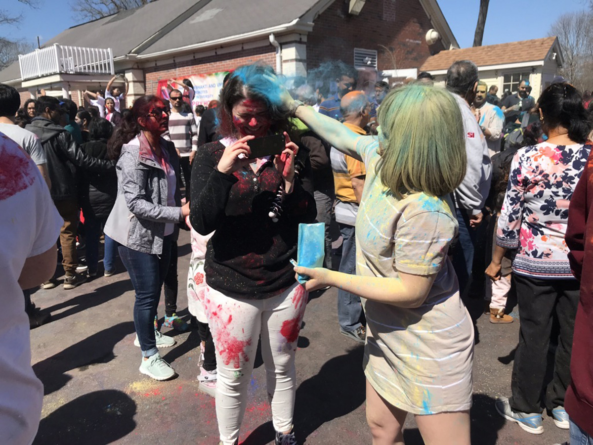 Student rubs blue pigment on other student