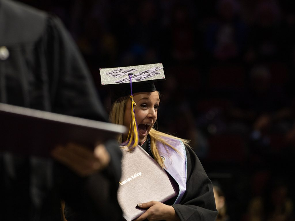 Woman in cap and gown shows off diploma