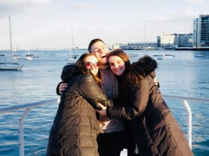 three friends hugging by harbor