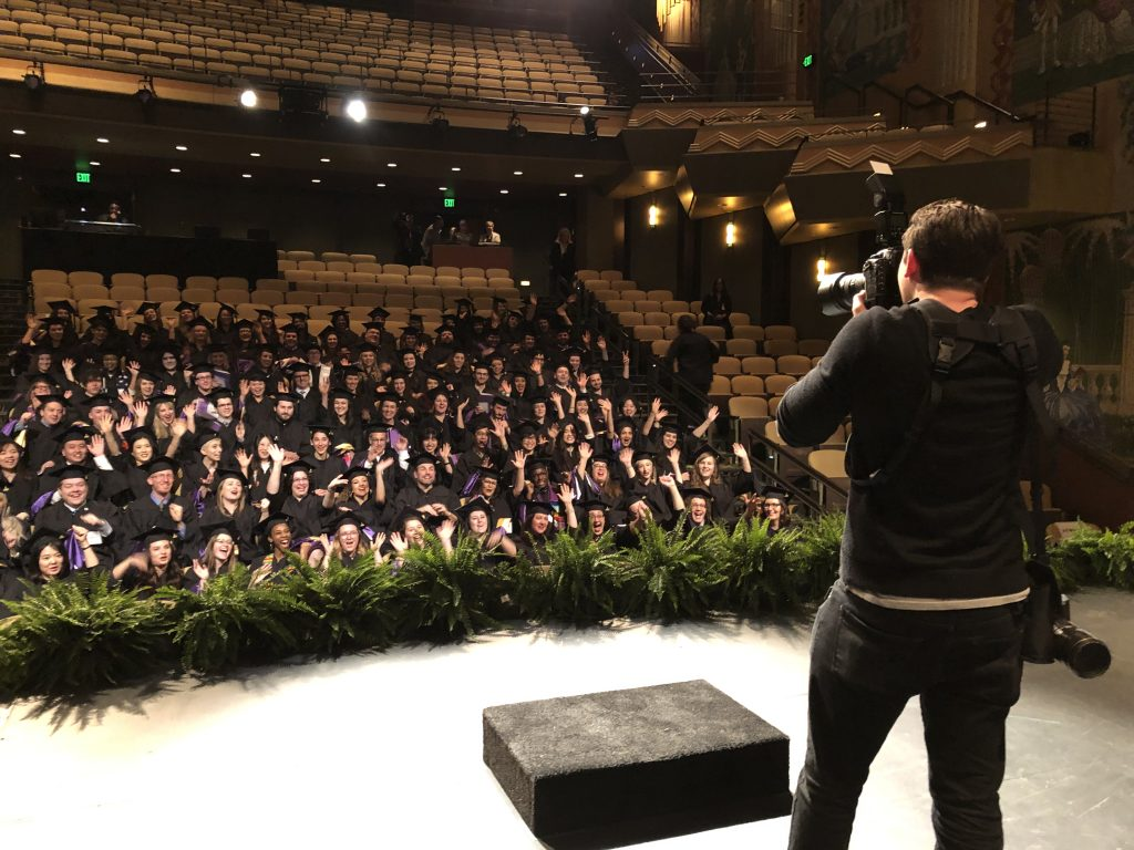 Derek Palmer, Staff Photographer for the Office of Marketing, takes photos of the graduating class sittin in the theatre.