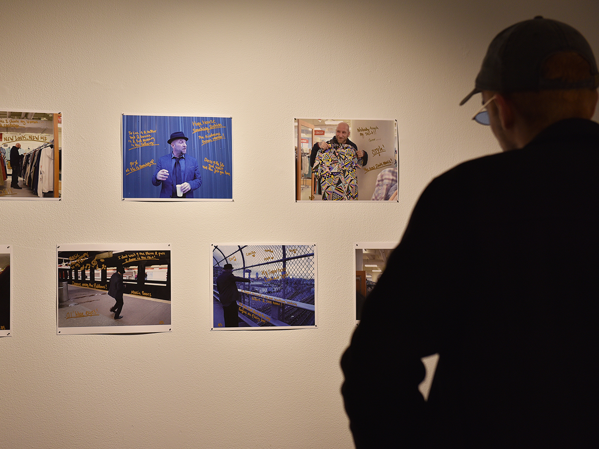 man looks at photos on wall
