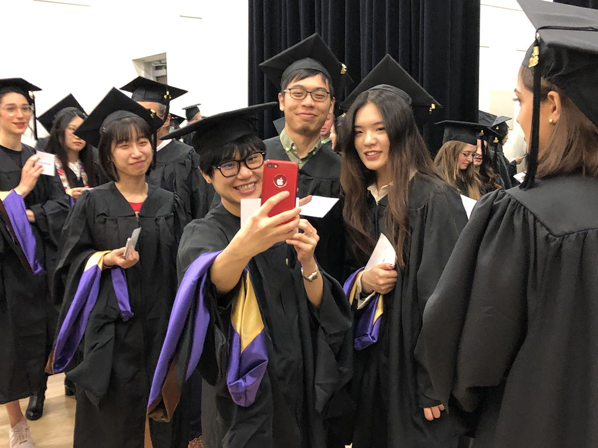 Students took selfies while waiting to go into the Paramount Theater for the School of the Arts Hooding Ceremony.