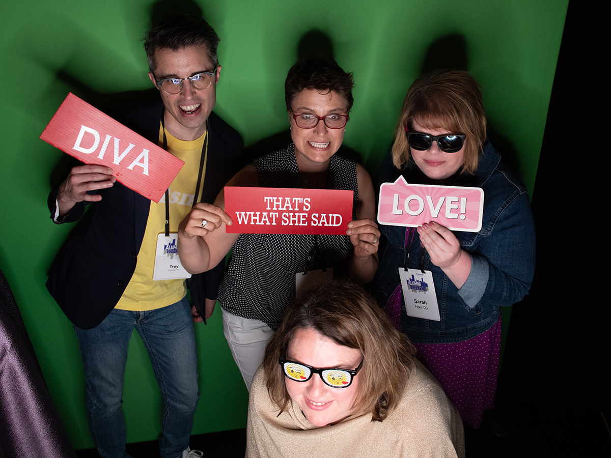 four holding signs in photo booth