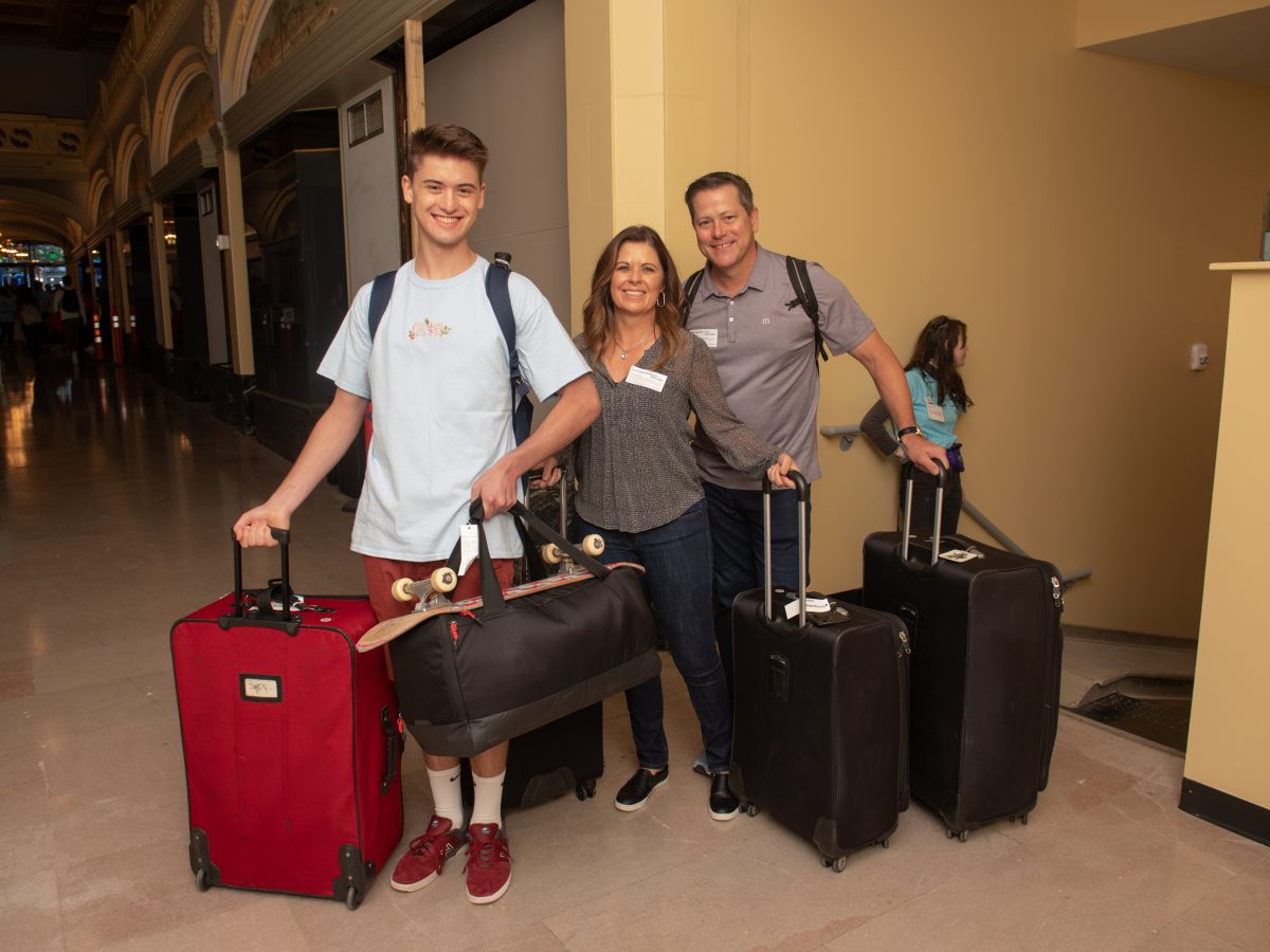 A student is helped by his parents with his luggage