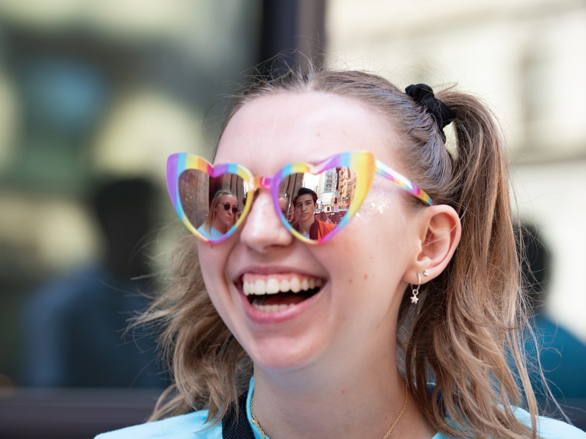 A student smiles while wearing sunglasses