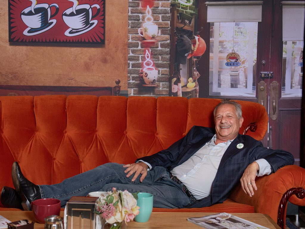 Kevin Bright '76 celebrates the 25th anniversary of Friends on a replica couch of the TV show's coffee shop. (Photo taken by Derek Palmer for Emerson College)