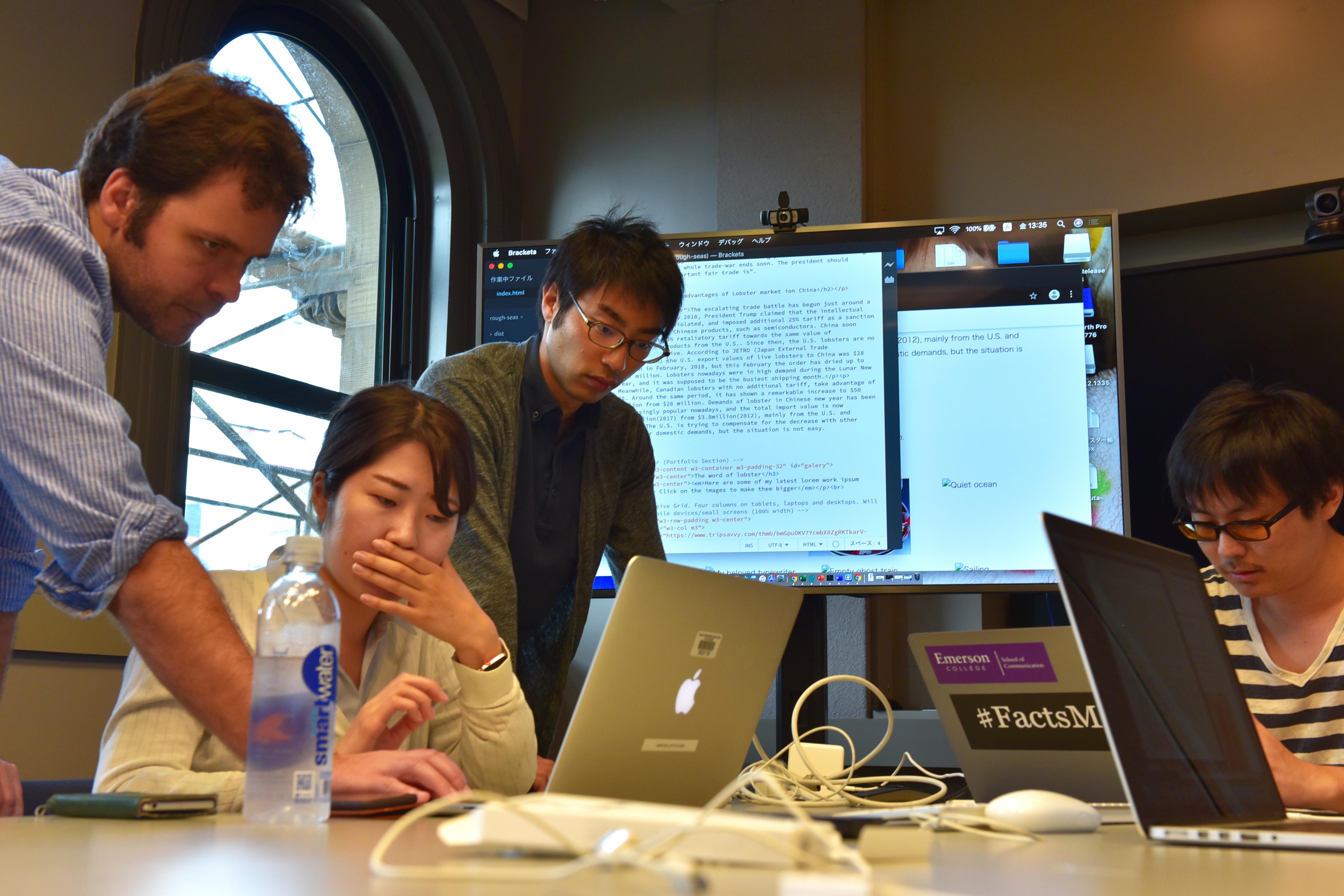 Professor looks at laptop screen of Yomiuri Shimbun journalists