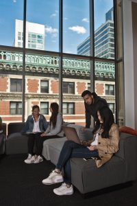 Students work in one of the new community rooms in the Little Building. (Photo by Derek Palmer for Emerson College)