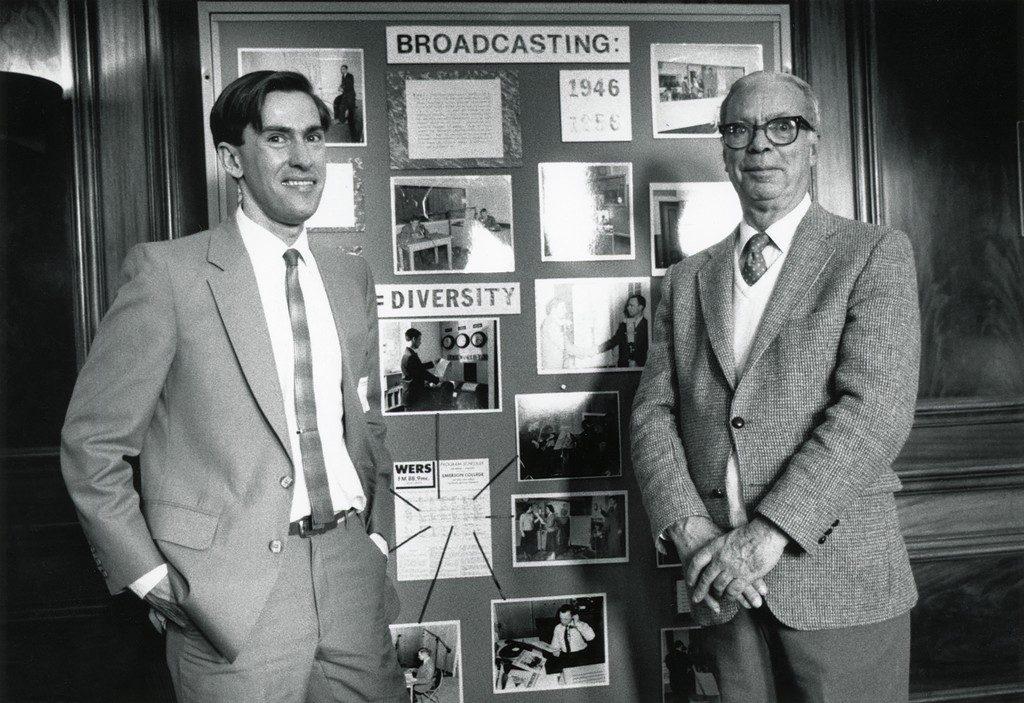 Two men in front of a bulletin board