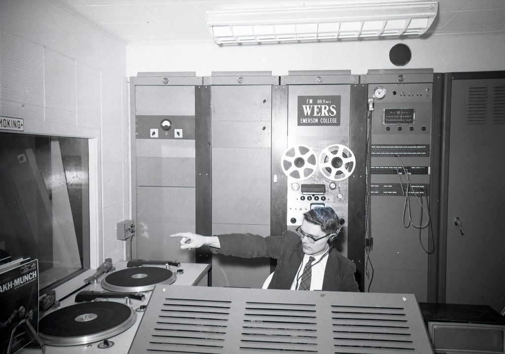 With turntables and a reel-to-reel deck behind him, a man points at someone else in the 1950s.
