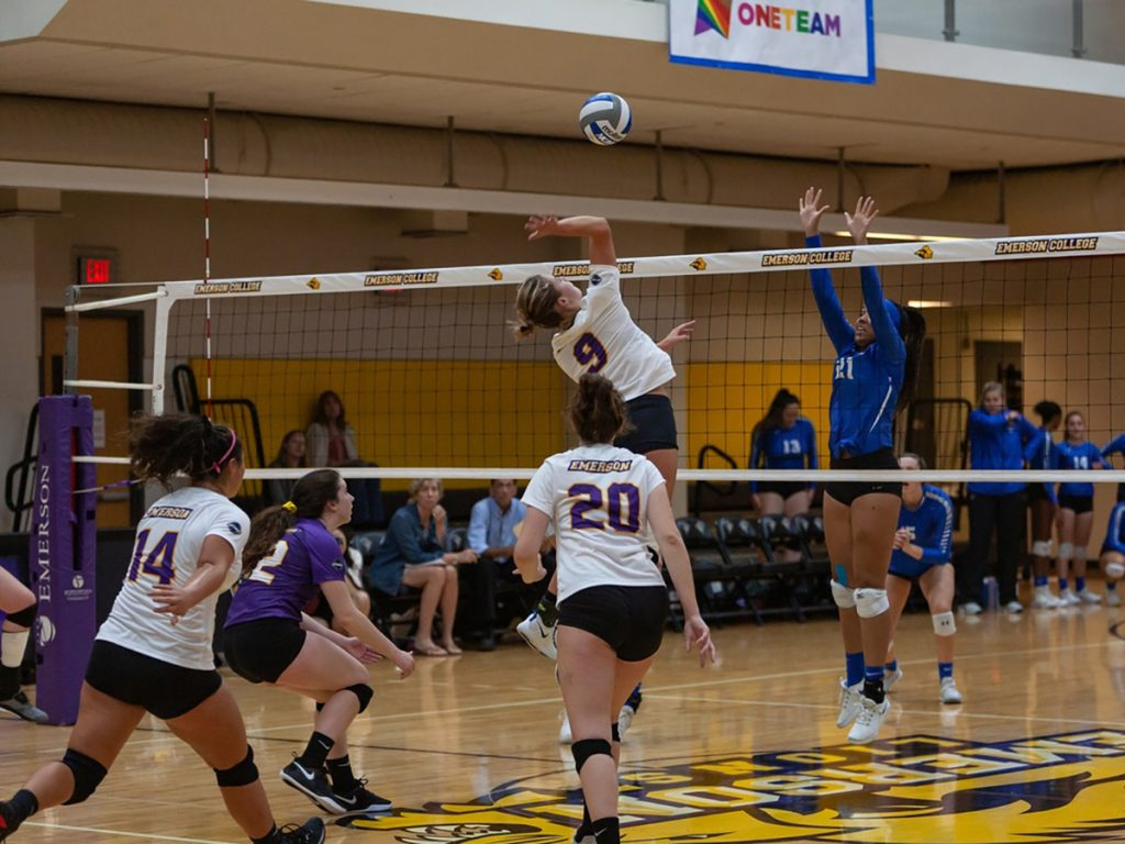 Carolyn Vaimoso jumps in the air to spike the volleyball over the net.
