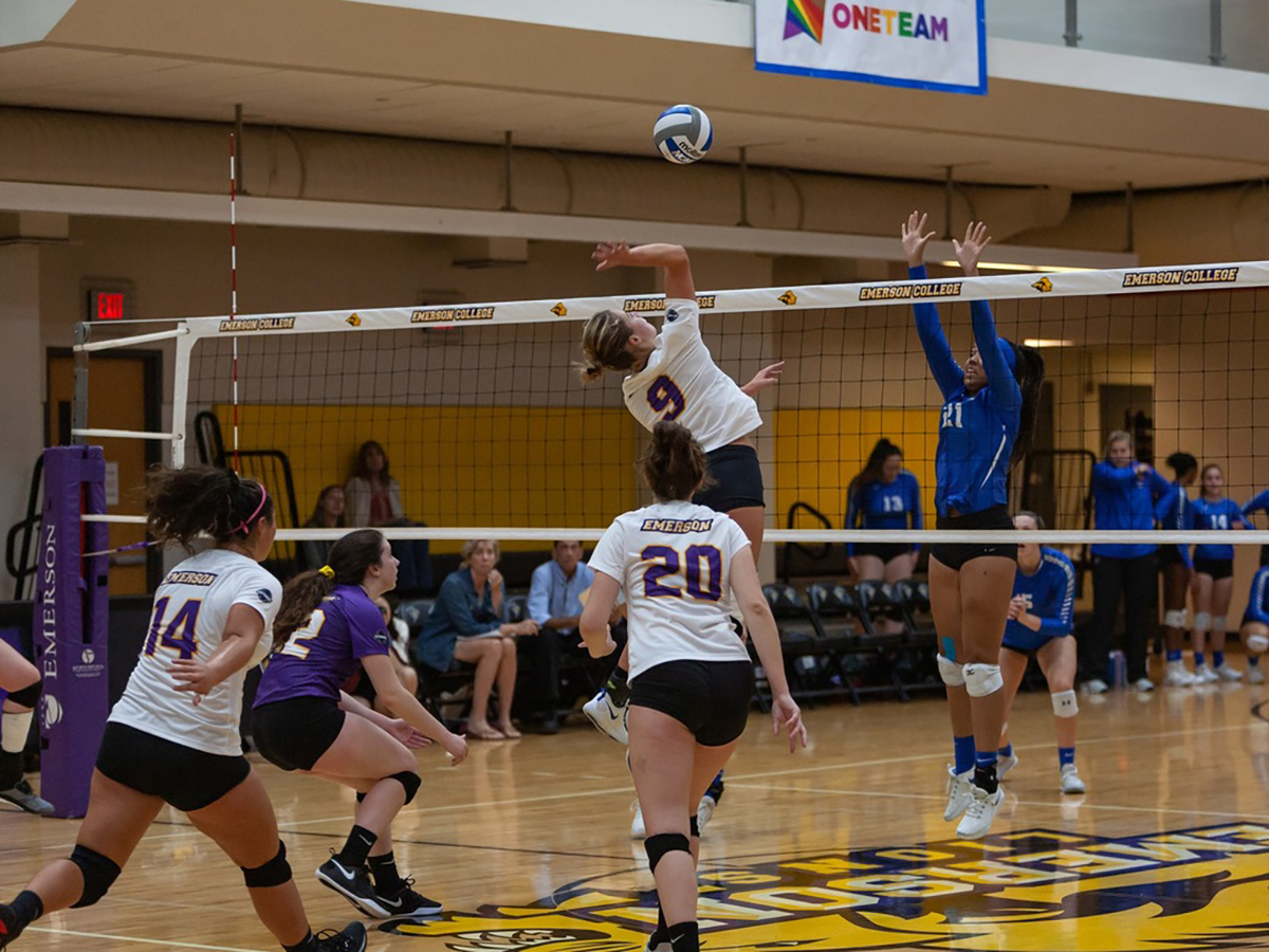 Carolyn Vaimoso jumps at the net to spike the volleyball.