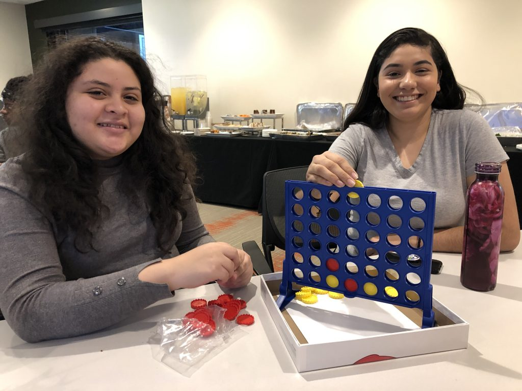 Kelly Moreno and Disneiruby Parra play Connect Four at a First Gen E-M event.