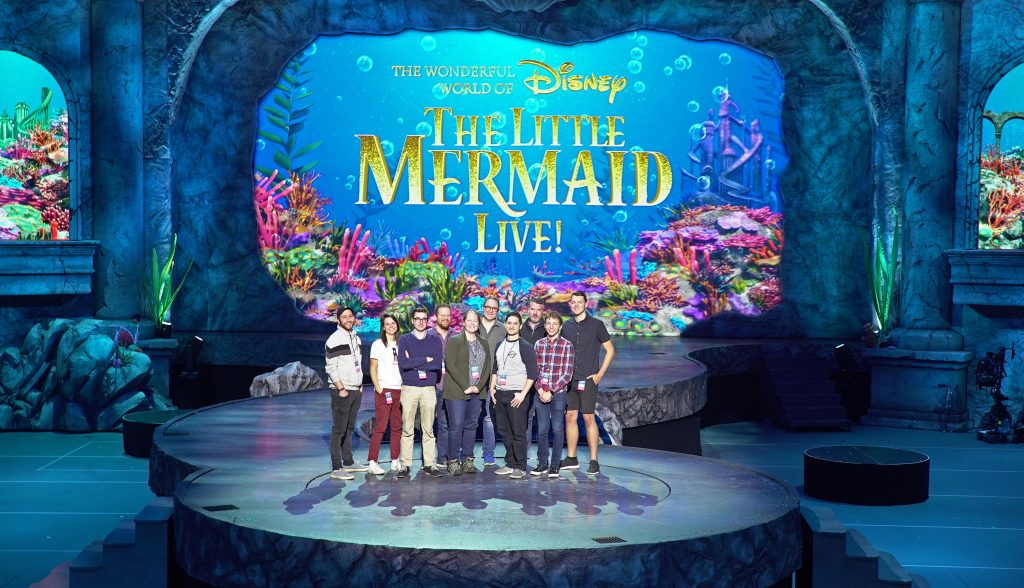 Emerson alum stand on the set of The Little Mermaid Live!