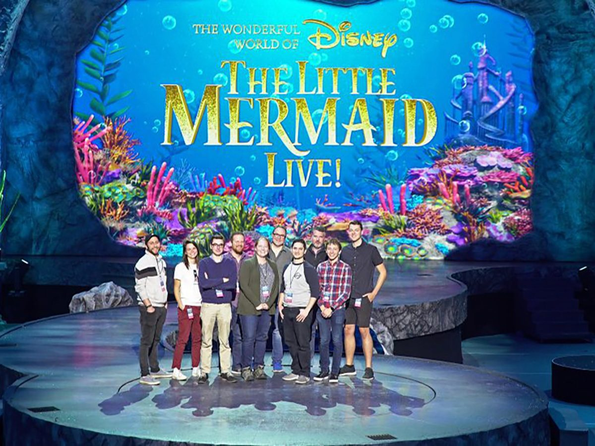 Emerson alums stand on the Little Mermaid set