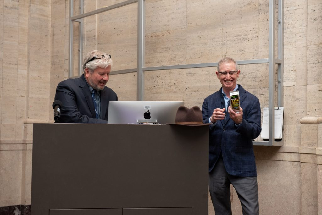 Bob Colby smiles while looking at a bag of coffee, and Tom Cooper looks down at a computer.