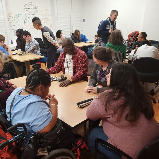 This image shows Emerson Communication Studies students working with high school students who are blind to help them learn podcasting.