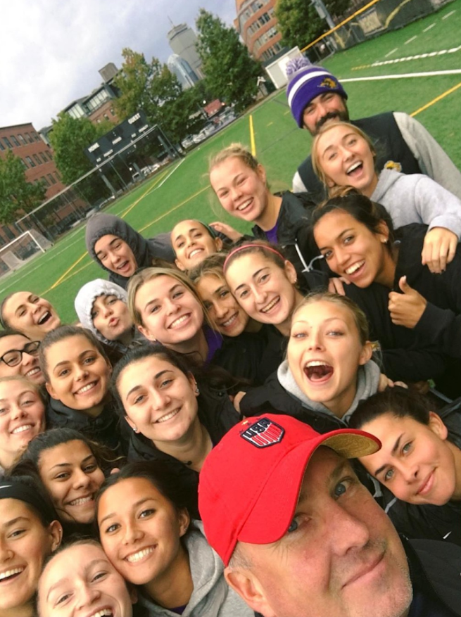 The women's soccer team takes a selfie with their coaches