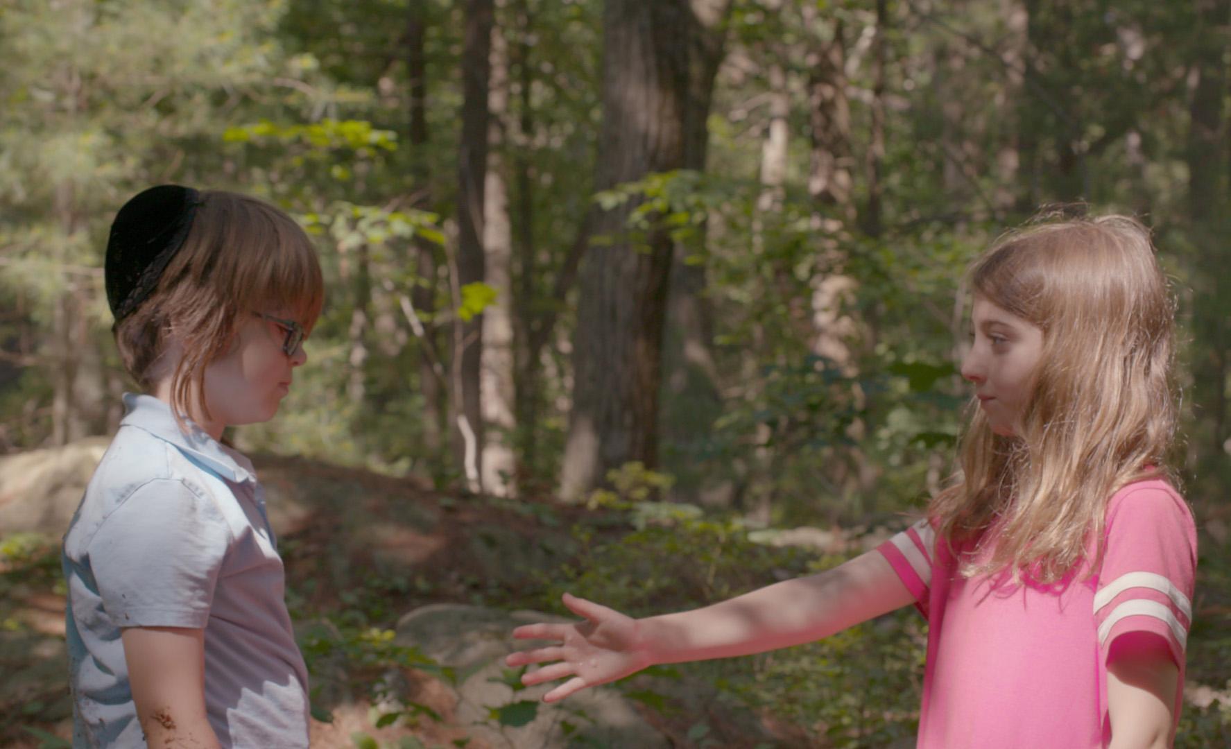 little girl extends hand to little boy in woods