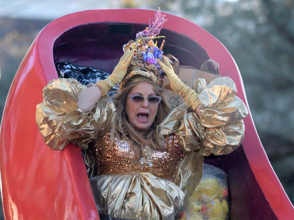 Jennifer Coolidge holds her crown on her head while roading in a float.