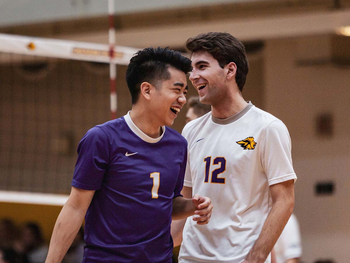 Two male volleyball players enjoy a laugh on the court